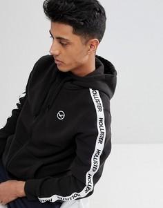 Худи черного цвета на молнии с лентой и логотипом Hollister Athletic - Черный