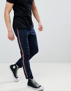 Темно-синие узкие брюки с отделкой кантом с ацтекским узором ASOS DESIGN - Темно-синий