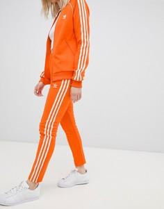 Оранжевые брюки-сигареты с тремя полосками Adidas Originals - Оранжевый
